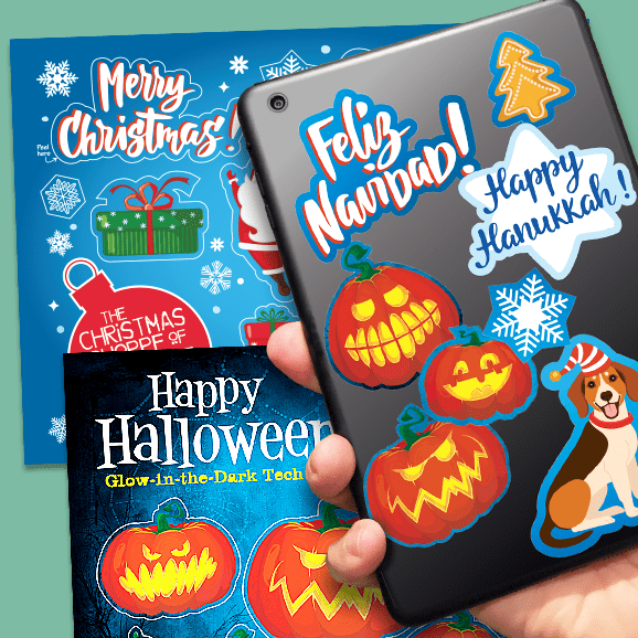 Hand holding tablet covered with tech tattoo labels with two sheets of holiday labels in background